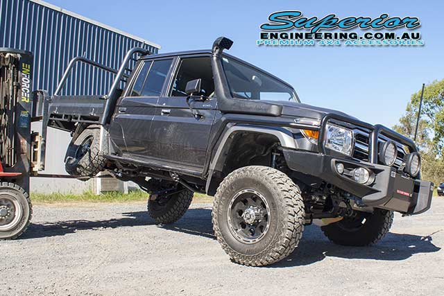 Front angle view of the 79 Series Toyota Landcruiser with the rear right coil suspension flexed up on the forklift